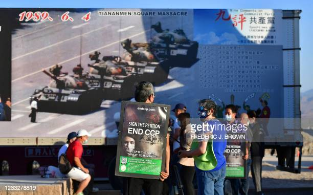 """Activists carry petitions to end the CCP in front of the iconic """"Tank Man"""" photograph on display at Liberty Sculpture Park in the Mojave desert town..."""
