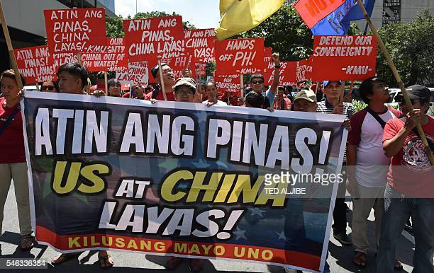 Activists carrying a antiChina and US placard march towards the Chinese consulate for a protest in Manila on July 12 ahead of UN tribunal ruling It...