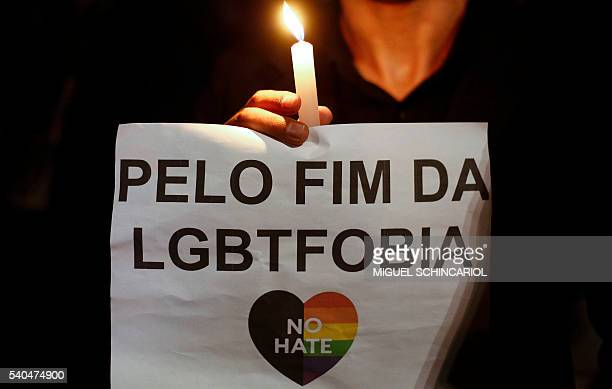 Activists carrying lit candles and flags participate in a vigil to pay tribute to the victims of the massacre occured at a gay club in Orlando in Sao...