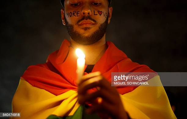 TOPSHOT Activists carrying lit candles and flags participate in a vigil to pay tribute to the victims of the massacre occured at a gay club in...
