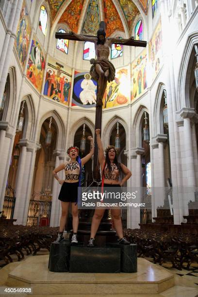 FEMEN activists chained to a cross protest against a reform of the country's abortion law at the Almudena Cathedra on June 13 2014 in Madrid Spain...