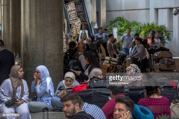 Activists demonstrate as international travelers arrive on the first day of the the partial reinstatement of the Trump travel ban temporarily barring...