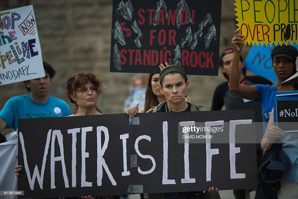 Activists demonstrate near a Hillary Clinton presidential campaign fundraiser featuring US President Barack Obama to call for a halt to the Dakota Access Pipeline project on October 24, 2016 in Beverly Hills, California. / AFP / DAVID