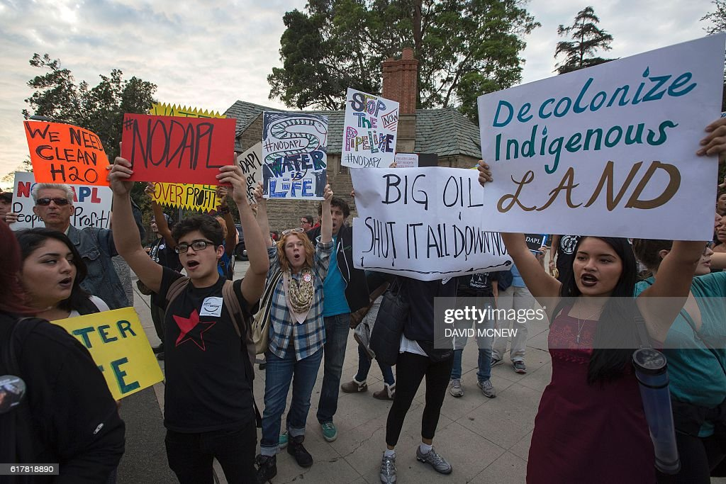 Activists demonstrate near a Hillary Clinton presidential campaign fundraiser with US President Barack Obama to call for a halt to the Dakota Access Pipeline project on October 24, 2016 in Beverly Hills, California. / AFP / DAVID