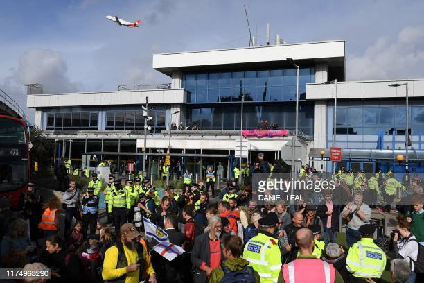 Activists demonstrate outside London City Airport during the fourth day of demonstrations by the climate change action group Extinction Rebellion, in...