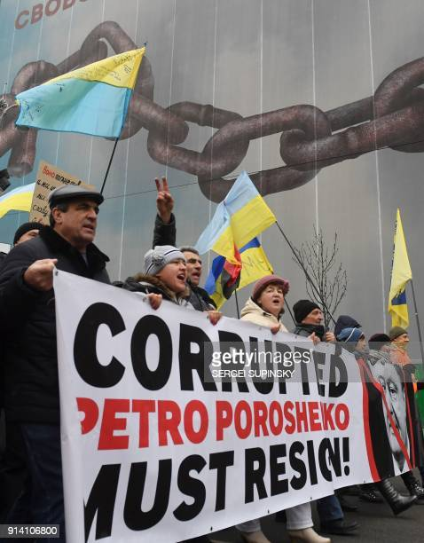 Activists display a banner depicting a crossedout Ukrainian President Petro Poroshenko and a slogan which states Corrupted Petro Poroshenko must...