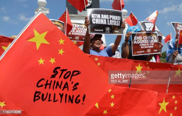 TOPSHOT Activists display antiChina placards and flags during a protest at a park in Manila on June 18 after a Chinese vessel last week collided with...