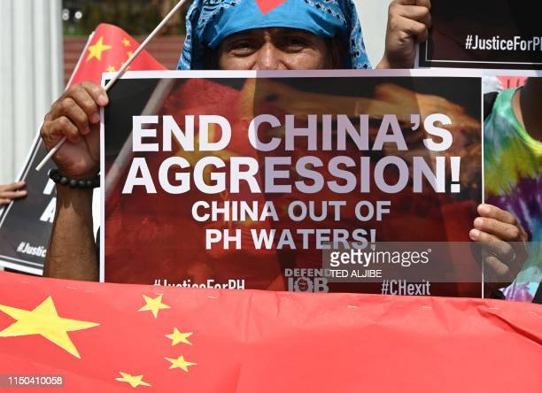 Activists display antiChina placards and flags during a protest at a park in Manila on June 18 after a Chinese vessel last week collided with a...