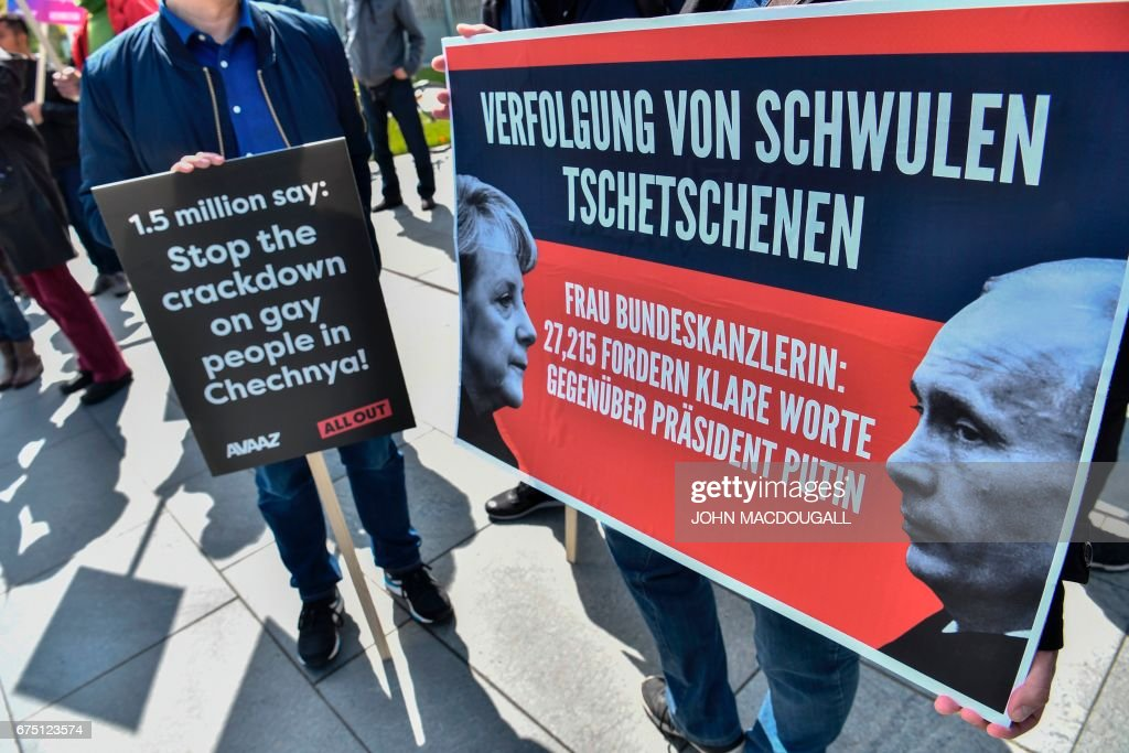 Activists display placards in front of the Chancellery in Berlin on April 30, 2017, during a demonstration calling on Russian President to put an end to the persecution of gay men in Chechnya. The protestors called on German Chancellor Angela Merkel, who will meet Putin in Sochi on May 2, 2017, to raise the issue with him. / AFP PHOTO / John MACDOUGALL