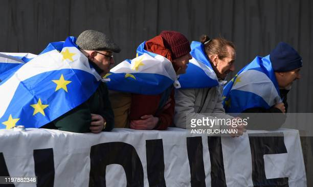 Activists, draped in Scottish Saltire flags with the stars of the EU flag, attend an anti-Conservative government, pro-Scottish independence, and...