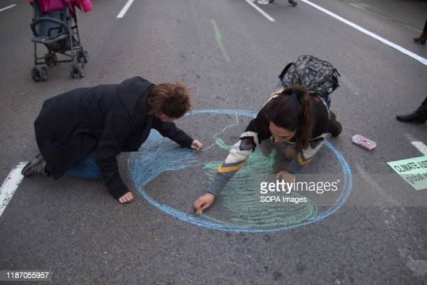 Activists draw the planet earth on the ground during the demonstration. Thousands of people from all over Europe protest in Madrid against COP25,...