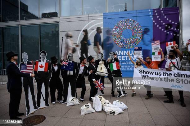 "Activists dressed as debt collectors"" hold cutouts of the leaders of United States, Joe Biden, Canada, Justin Trudeau, Australia, Scott Morrison,..."