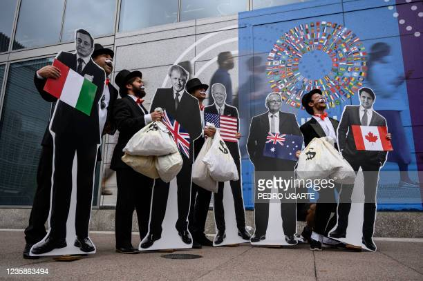 """Activists dressed as debt collectors"""" hold cutouts of the leaders of Italy, Mario Draghi, United Kingdom, Boris Johnson, United States, Joe Biden,..."""