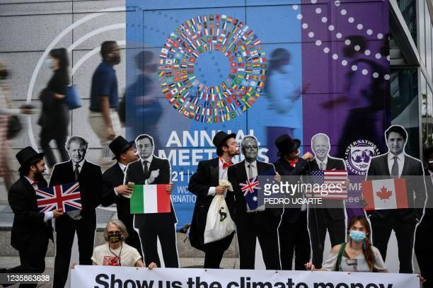 "Activists dressed as debt collectors"" hold cutouts of the leaders of United Kingdom, Boris Johnson, Italy, Mario Draghi, Australia, Scott Morrison,..."