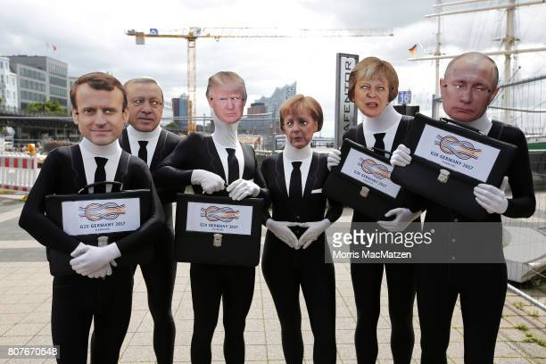 ATTAC activists dressed as G20 leaders pose for a photo during a protest action at the harbour prior to the G20 Summit in Hamburg on July 4 2017 in...