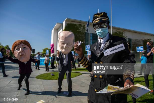 Activists dressed as German Chancellor Angela Merkel and Finance Minister Olaf Scholz take part in a protest outside the Chancellery against the...