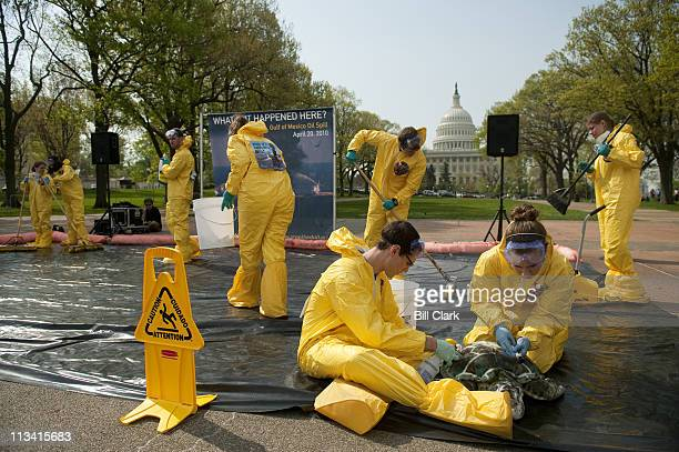 Activists dressed as oil cleanup workers pretend to mop up oil and clean a stuffed turtle as Oceana holds a rally in Upper Senate Park on Wednesday...