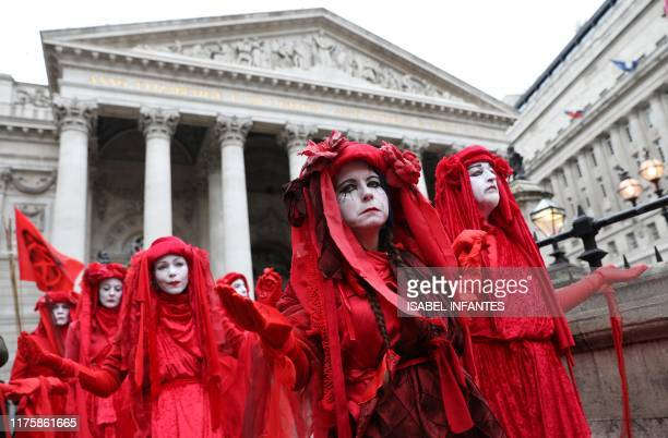 Activists dressed in red demonstrate outside of the Royal Exchange opposite the Bank of England during the eighth day of demonstrations by the...