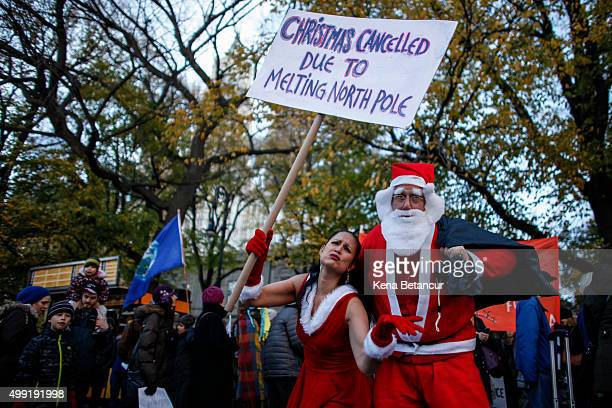 Activists dressed up as Santa Claus hold a banner as they take part in a global climate march at City Hall on November 29 2015 in New York City The...