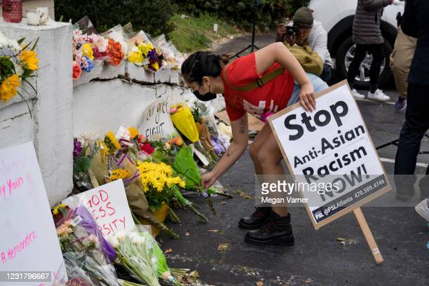 Activists drop flowers during a demonstration against violence against women and Asians following Tuesday night's shooting on March 18, 2021 in...