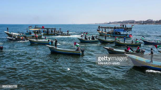 Activists escort a blockaderunning boat carrying Palestinian students and others injured during protests out to sea from the Gaza City harbour on...