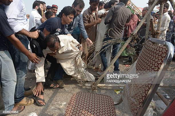 Activists for Pakistani opposition politician Imran Khan stop a supporter from going past a barbed wire cordon during an antigovernment march in...