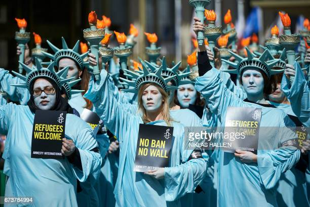 TOPSHOT Activists from Amnesty dressed as the Statue of liberty take part in a demonstration to mark the first 100 days in office of US President...