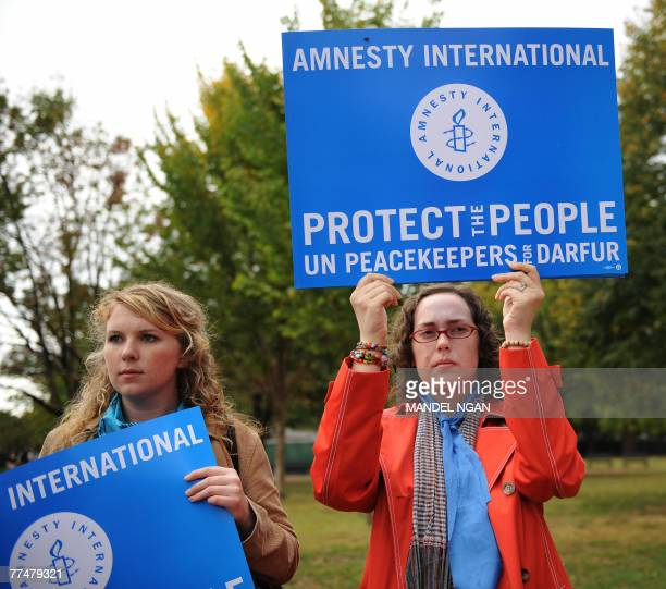 Activists from Amnesty International holds placards during a rally and vigil for the people of Sudan's Darfur region 24 October 2007 at Lafayette...