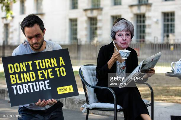 Activists from Amnesty International posing as British Prime Minister Theresa May and victims of torture hold a demonstration on Whitehall outside...