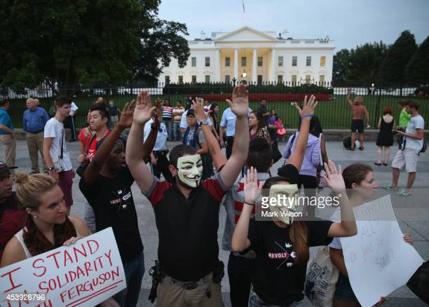 Activists from Anonymous raise their hands as theyt participate in a Day Of Rage protest in front of the White House August 21 2014 in Washington DC...