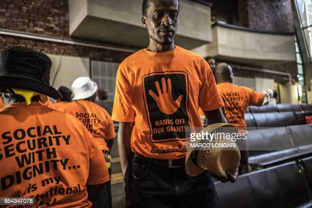 Activists from Black Sash a South African human rights NGO gather at the Constitutional Court on March 17 in Johannesburg as they wait for a ruling...