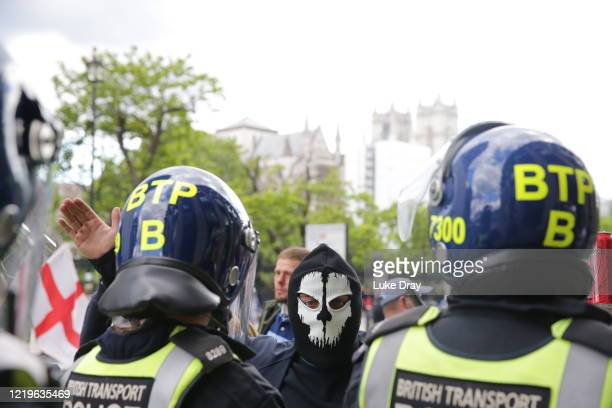 Activists from far-right linked groups face police officers at Parliament Square on June 13, 2020 in London, England. A number of anti-racism...
