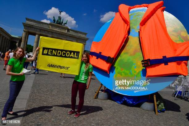 Activists from Greenpeace display a banner next to a giant globe dressed with a lifejacket during a protest outside the venue of the 8th Petersberg...
