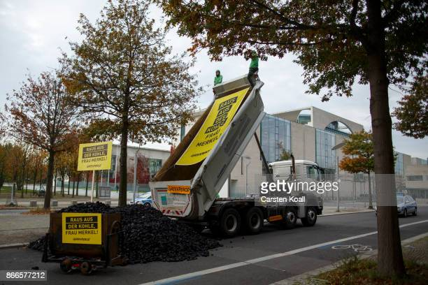 Activists from Greenpeace sitting on a truck next to 10 tons of coal they dumped in front of the Chancellery to protest the coal energy policy stance...