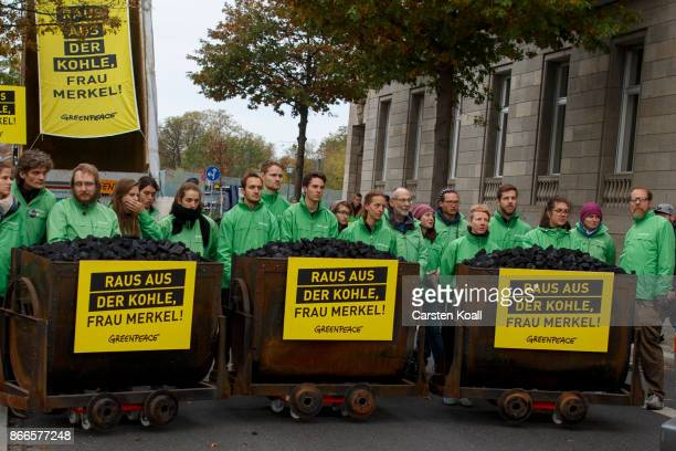 Activists from Greenpeace stay behind coal wagons next to 10 tons of coal they dumped in front of the Chancellery to protest the coal energy policy...