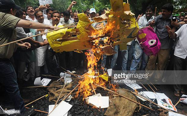 Activists from India's main opposition Bharatiya Janatha Party burn an effigy of Indian Prime Minister Manmohan Singh during a protest against the...