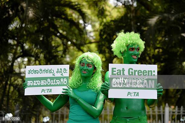 Activists from NGO People for Ethical Treatment of Animalspose painted in green hold 'Go Green' placards in Bangalore on March 16 as they take part...
