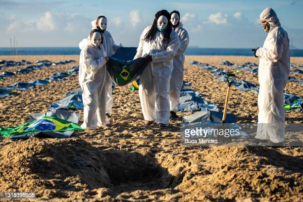 Activists from NGO Rio de Paz carry a Brazilian flag as they display hundreds of plastic bags, representing dead bodies during an event to pay homage...