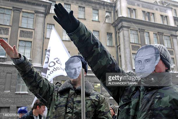 Activists from Oborona a young group backed by the liberal Union of Right Forces and Yabloko salute wearing masks with the faces of Russian President...