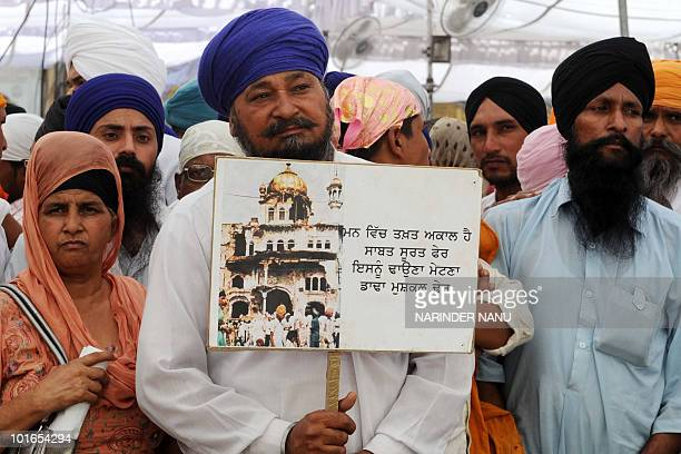 Activists from radical Sikh organisations hold a picture of the damaged Sri Akal Takht in 1984 during an 'Operation Bluestar' anniversary protest at...