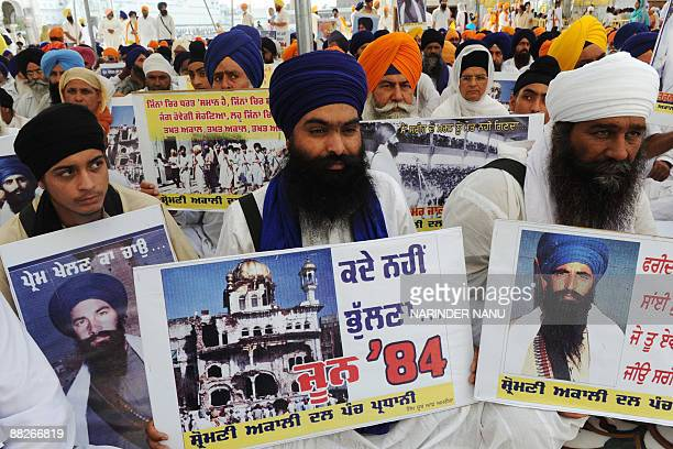Activists from radical Sikh organizations hold placards displaying images of the 1984 damage to the shrine Sri Akal Takht Sahib and portraits of Sant...