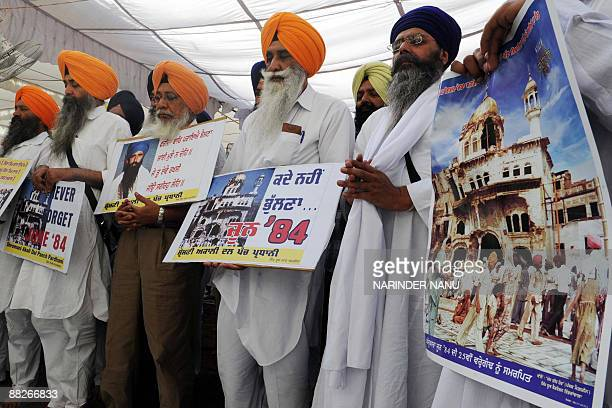 Activists from radical Sikh organizations hold placards displaying images of the 1984 damage to the shrine Sri Akal Takht Sahib and a portrait of...