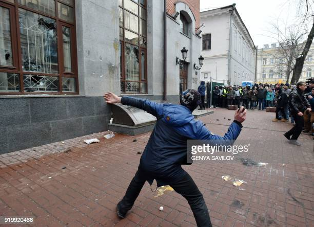 TOPSHOT Activists from several Ukrainian ultranationalist parties throw stones and eggs at the windows of Rossotrudnichestvo building in Kiev on...