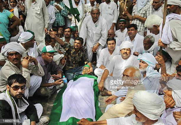 Activists from the Bhartiyaa Kisan Union conduct a fast with the body of Katar Singh, who died during their protest against land acquisition by the...