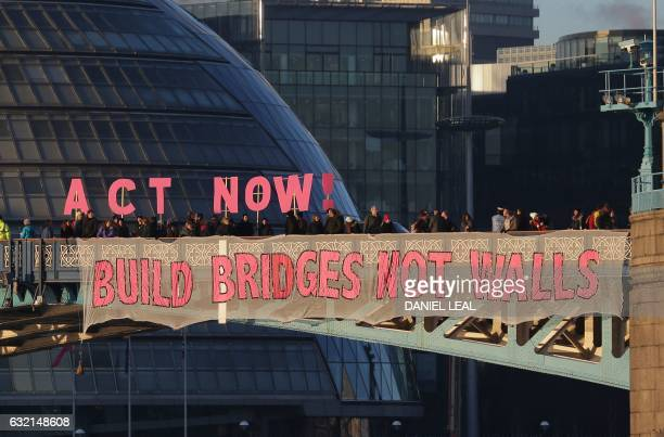 TOPSHOT Activists from the Bridges not Walls movement display messages on Tower Bridge in London on January 20 2017 to coincide with the inauguration...