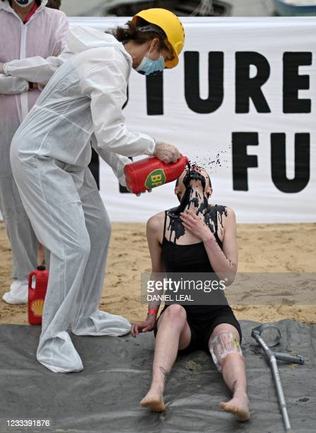 Activists from the climate change protest group Extinction Rebellion, pour a black liquid to represent oil, into the mouth of a fellow acivist as...