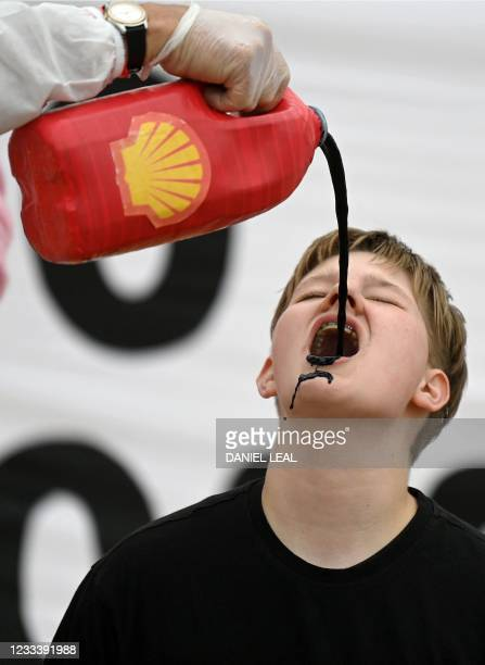 Activists from the climate change protest group Extinction Rebellion, pour a black liquid to represent oil, into the mouth of a fellow activist as...
