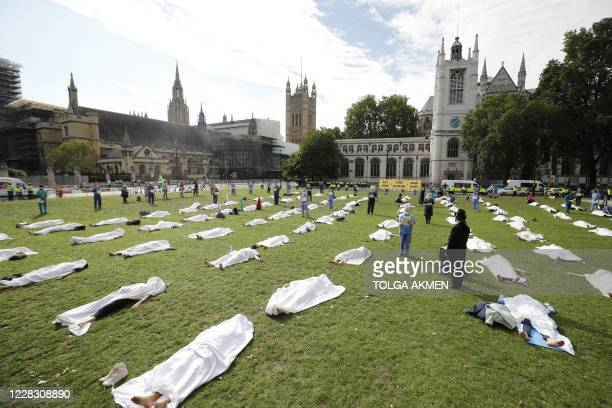 """Activists from the climate protest group Extinction Rebellion perform a theatrical """"die in"""" on the Green at Parliament Square central London in front..."""