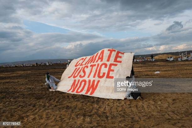 Activists from the collective Ende Gelande seen holding a large banner written on it 'Climate Justice Now' on the mine site during a demonstration...