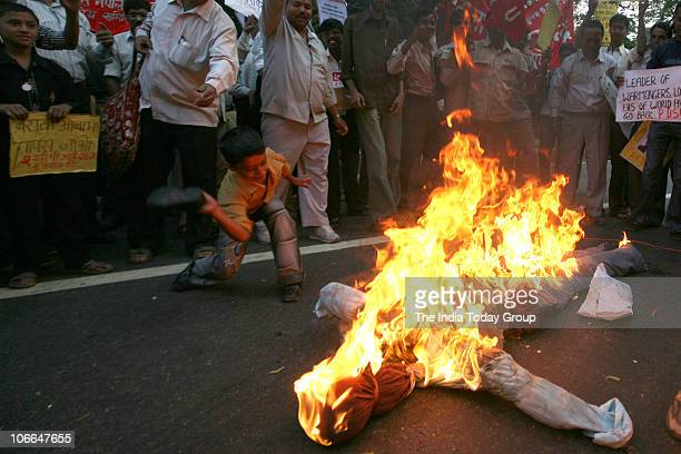 Activists from the Communist Party of India hold a poster bearing US President Barack Obama's portrait as they burn an effigy symbolizing 'US...